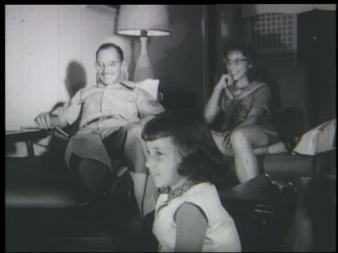 stockvideo's en b-roll-footage met b/w 1961 father + daughters sitting in living room watching television + smiling - 1961