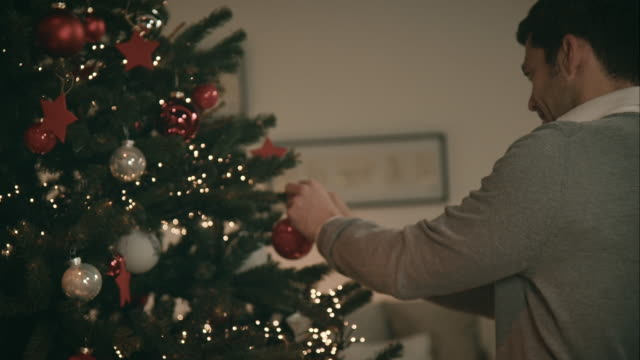 Father decorating christmas tree
