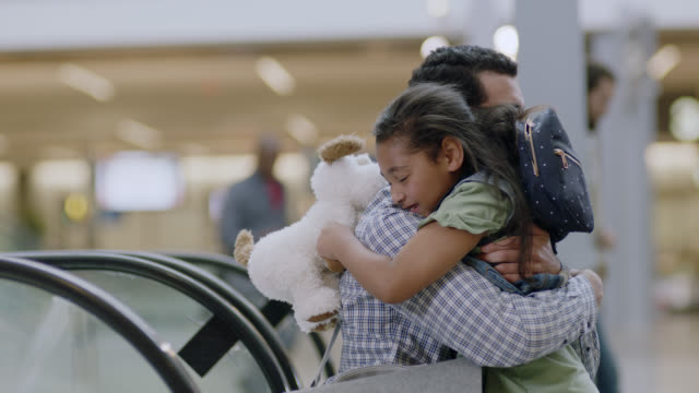 vidéos et rushes de father descends escalator with gift to embrace young daughter at airport arrivals. - débarquement