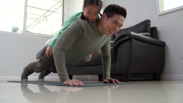 vídeos y material grabado en eventos de stock de father doing push ups with happy dougther on his back at home.man exercising with little girl together - flexiones