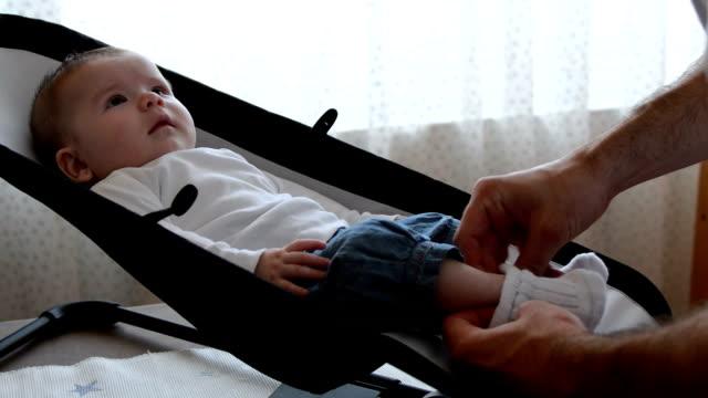 stockvideo's en b-roll-footage met father dresses baby daughter sitting in rocker - schommelen schommelstoel