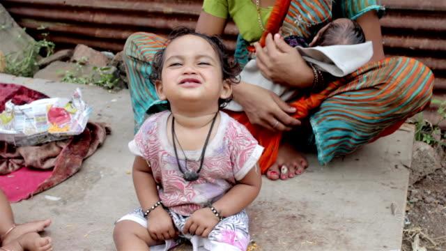 padre di vestire sua figlia in rurale famiglia indiana - fame video stock e b–roll