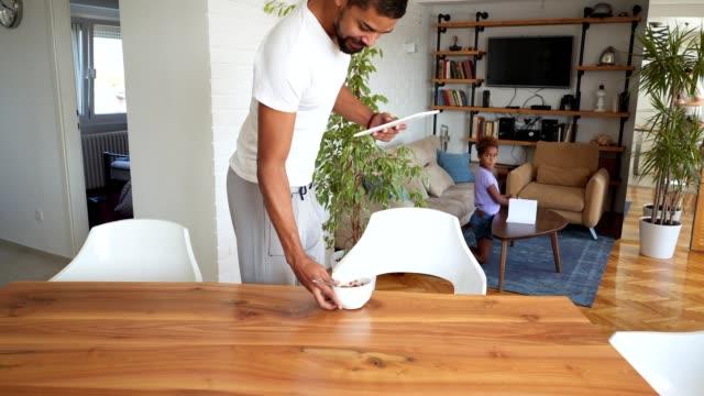 vidéos et rushes de père petit déjeuner alors que la fille est fait ses devoirs. - genderblend