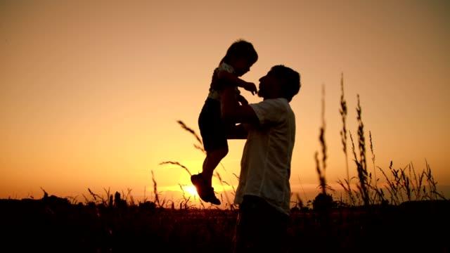 vídeos de stock, filmes e b-roll de slo mo pais abraçam seu filho ao pôr-do-sol - flutuar no ar