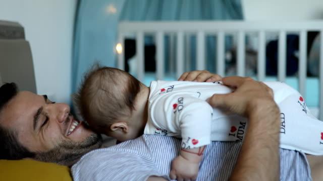stockvideo's en b-roll-footage met vader omhelst babyjongen - genderblend