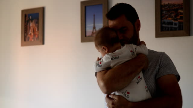 father embracing baby - stringere tenere video stock e b–roll