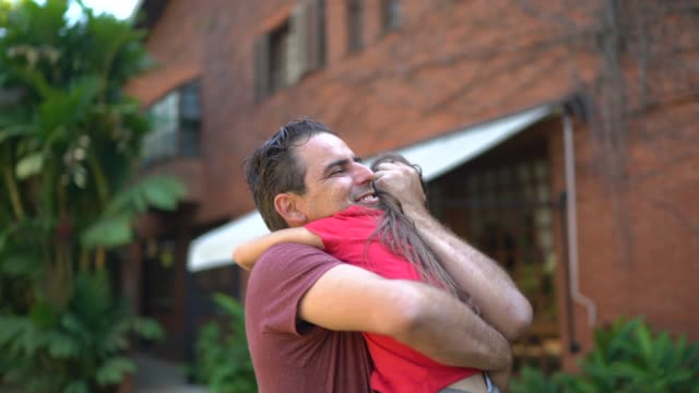 father embracing daughter in the backyard at home - offspring stock videos & royalty-free footage