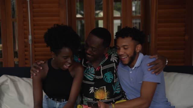 vídeos de stock, filmes e b-roll de pai que abraça o irmão, usando o smartphone - família de duas gerações