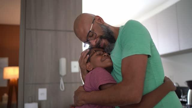 vídeos de stock, filmes e b-roll de pai abraçando o filho em casa - cobrindo