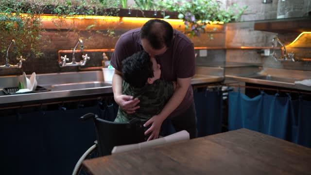 vídeos de stock, filmes e b-roll de pai abraçando filho usando cadeira de rodas em casa - carinhoso