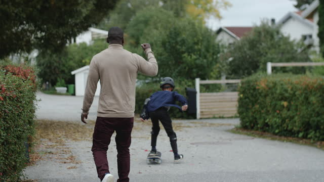 stockvideo's en b-roll-footage met father encouraging while cheering son skateboarding on road - shaky