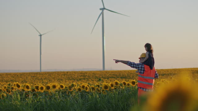 a father engineer holds his daughter in his arms and runs between the wind turbines with great freedom in the sunflower field. - childhood stock videos & royalty-free footage