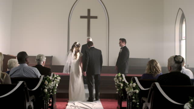 father escorting bride to the groom at the front of a chapel. - father of the bride stock videos and b-roll footage