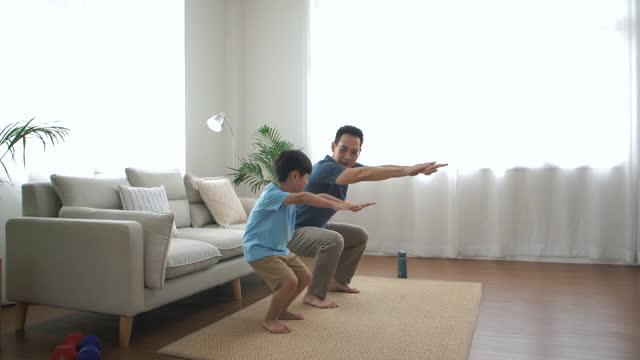 vidéos et rushes de le père fait de l'exercice avec son fils dans le salon - son