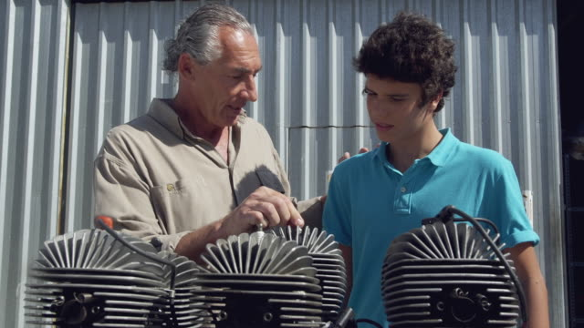 MS Father explaining function of machine part to son (14-15) / Near Torre del Mar, Malaga, Spain