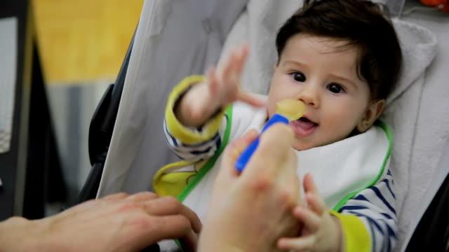 vídeos de stock e filmes b-roll de pai feedig seu bebé menino - alimentar