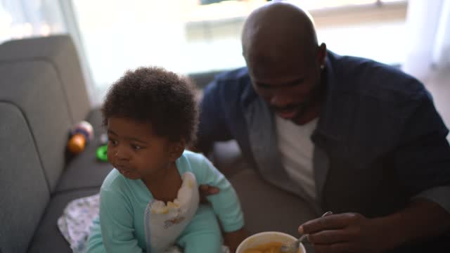 father feeding baby son at home - genderblend stock videos & royalty-free footage