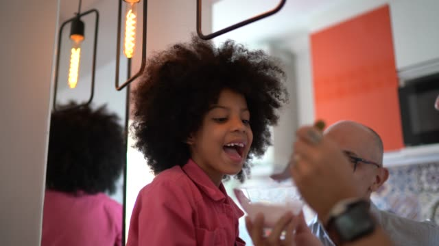 father feeding daughter with yogurt at home - yoghurt stock videos & royalty-free footage