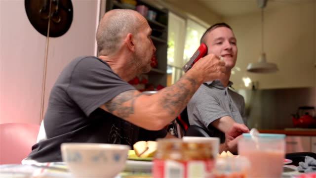 vídeos de stock e filmes b-roll de father feeding disabled son - paralisia