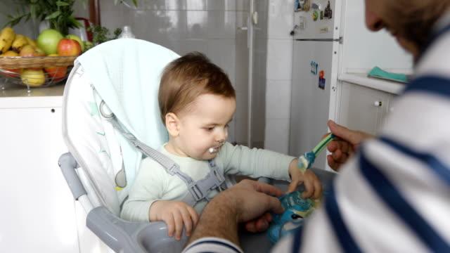 vídeos de stock, filmes e b-roll de pai alimentando seu filho bebê - comida de bebê