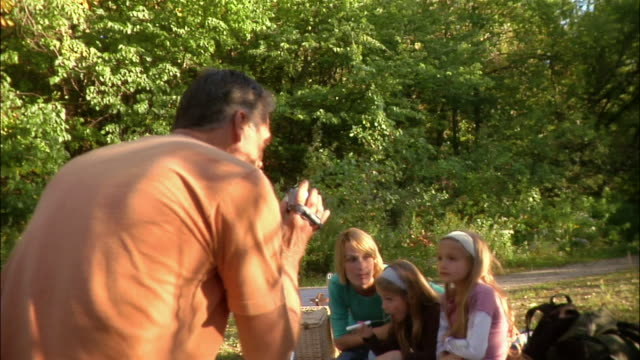 father filming family picnic wth digital camcorder - digital camcorder stock videos & royalty-free footage