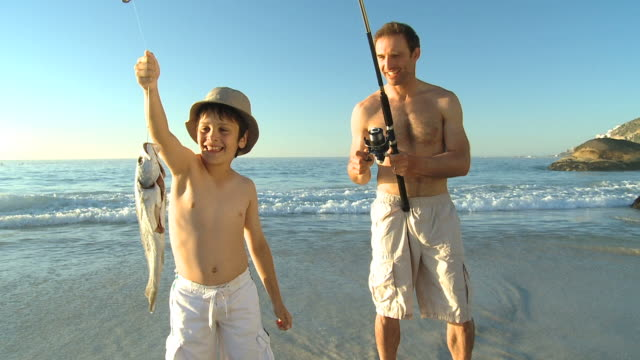 WS Father fishing with boy on beach / Cape Town, Western Cape, South Africa