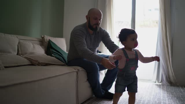 father following daughter's first steps at home - genderblend stock videos & royalty-free footage