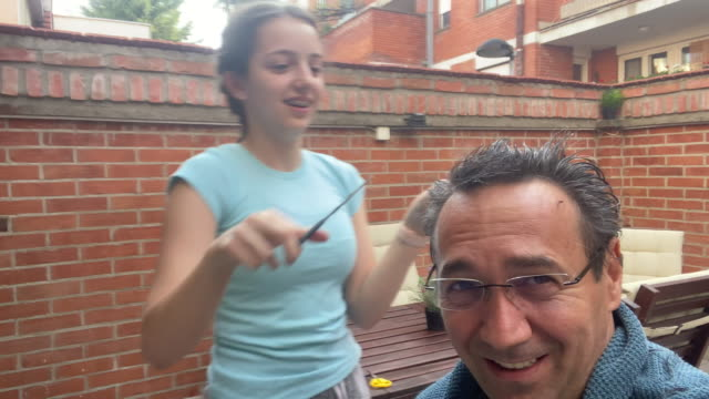 father getting a haircut from daughter at home during coronavirus quarantine - fun stock videos & royalty-free footage
