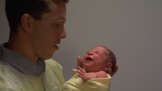 CU, Father getting new born baby from doctor hands