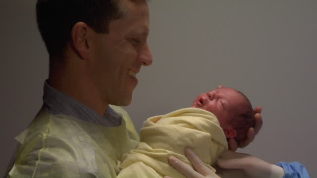 cu, father getting new born baby - genderblend stock-videos und b-roll-filmmaterial