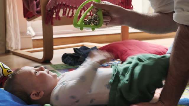 vídeos de stock, filmes e b-roll de father gives his son a rattle to play with while he is changing clothes. - vida de bebê