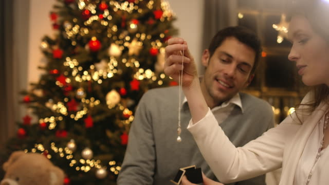 father gives mother present on christmas eve - necklace stock videos & royalty-free footage