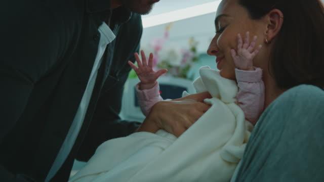 vater gibt baby zu mutter auf dem bett im krankenhaus - geben stock-videos und b-roll-filmmaterial