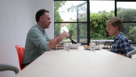 stockvideo's en b-roll-footage met father giving his son some salad with a meal - alleenstaande vader