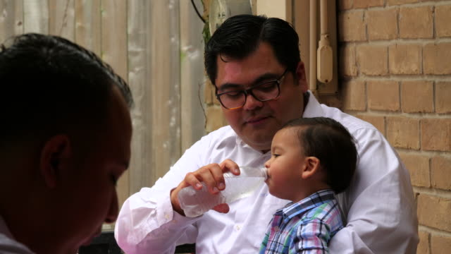MS Father giving infant son drink of water during family birthday party