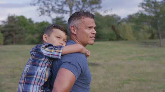 stockvideo's en b-roll-footage met vader geven zoon een piggy-back ride in een park - menselijke rug