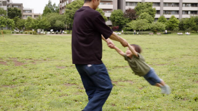 father grabs his little son's hands and spins with fun - lawn stock videos & royalty-free footage
