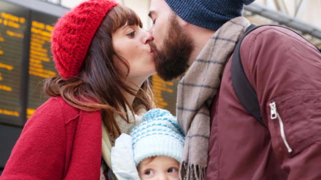 father greets and kisses mother and son at railway station. - ホームカミング点の映像素材/bロール