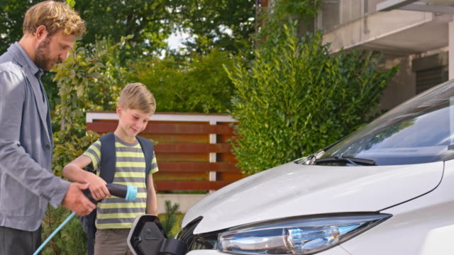 SLO MO Father handing son plug to charge car
