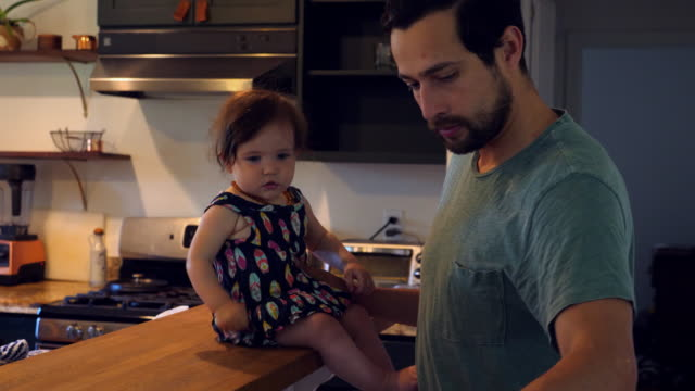 ms father hanging out with young son and infant daughter in kitchen - ジェンダーブレンド点の映像素材/bロール