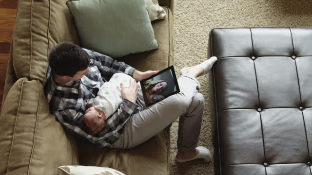 stockvideo's en b-roll-footage met ha ms pan father having video conference using digital tablet, sitting with baby son (0-1 months) on sofa / lehi, utah, usa - videogesprek