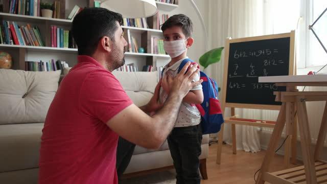 vídeos de stock e filmes b-roll de father help her boys wearing face mask for protection coronavirus outbreak - família com um filho