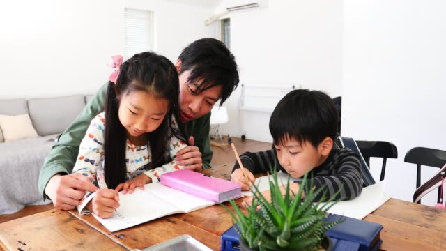 father helping children to do their homework - homework stock videos & royalty-free footage