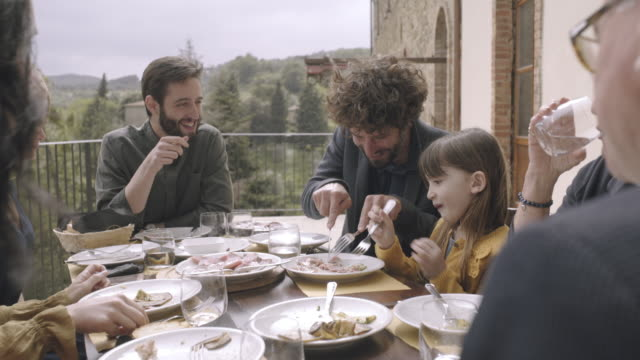 father helping daughter at family meal - italien stock-videos und b-roll-filmmaterial