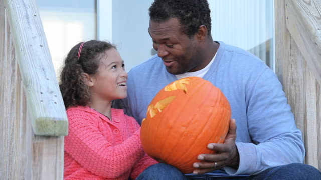 MS Father helping daughter (6-7) carving jack o' lantern on porch / Richmond, Virginia, USA