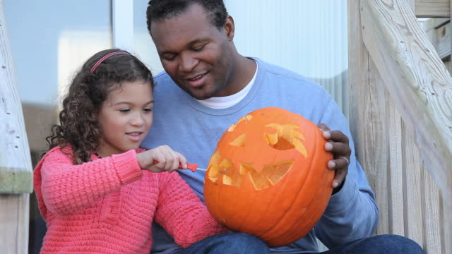 vidéos et rushes de ms tu father helping daughter (6-7) carving jack o' lantern on porch / richmond, virginia, usa - sculpture produit artisanal