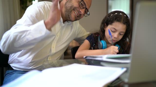 stockvideo's en b-roll-footage met vader die dochter helpt die haar thuiswerk doet op videopraatje e-learning - e learning