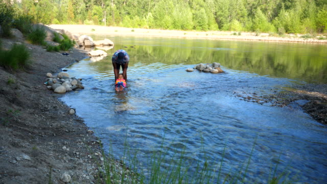 ws father helping daughter float in river on summer afternoon - life jacket stock videos & royalty-free footage