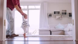 Father helping daughter learn to walk at home, side view