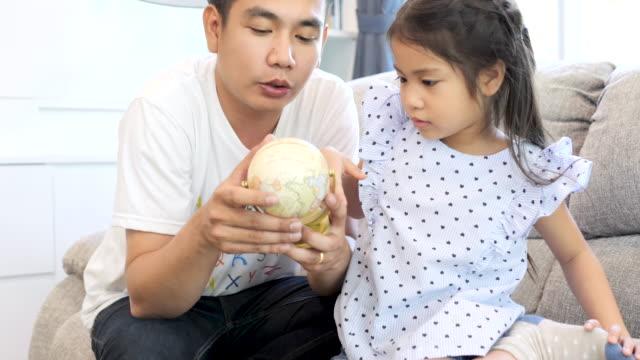 vídeos y material grabado en eventos de stock de padre ayudando a su hija a aprender con un globo terráqueo en la sala de estar. - espacio y astronomía